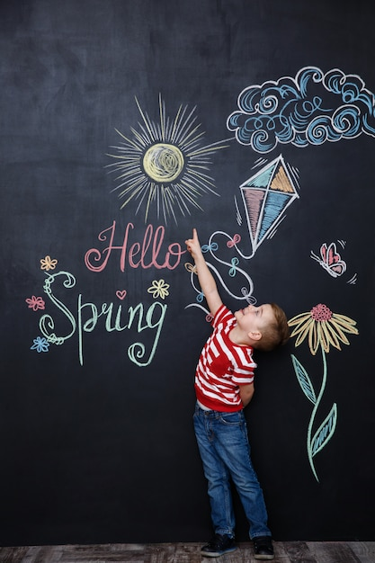 Cheerful young kid standing and pointing at the hello spring Free Photo