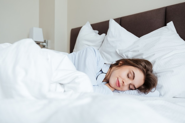 Cheerful young lady dressed in pajama sleeping in bed Free Photo