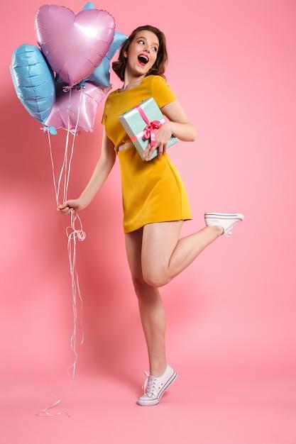 선물로 풍선을 들고 노란 드레스에 쾌활 한 아가씨 무료 사진