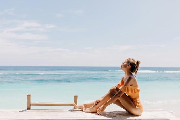 Веселая барышня сидит на пляже летним утром. снимок красивой девушки в оранжевых купальниках, позирующей на пляже Бесплатные Фотографии