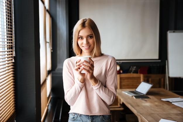 コーヒーを飲みながらカフェに立っている陽気な若い女性 無料写真