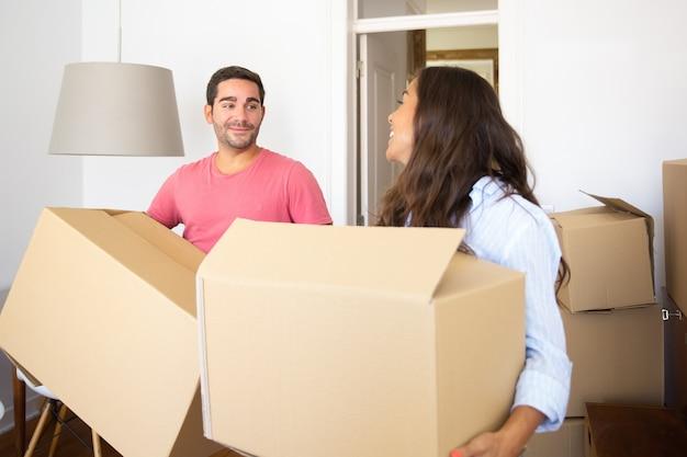 彼らの新しいアパートでカートンボックスを運び、話し、笑う陽気な若いラテンカップル 無料写真