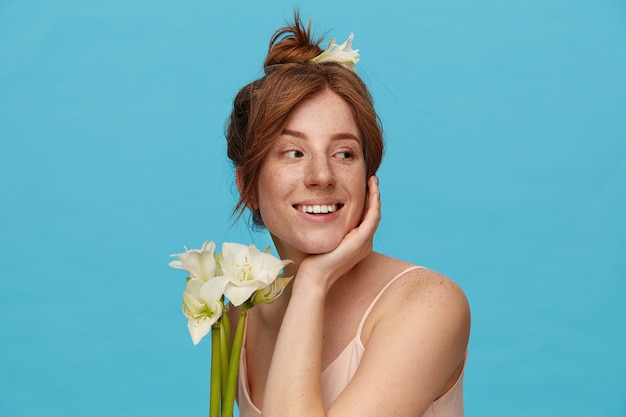 Cheerful young lovely redhead female leaning her head on raised hand and looking positively aside with pleasant smile, standing over blue background with flowers Free Photo