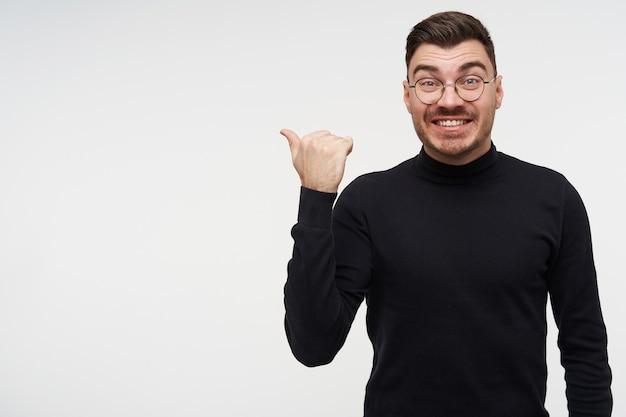 Веселый молодой симпатичный короткошерстный бородатый брюнет, указывая в сторону с поднятой рукой и радостно глядя с широкой улыбкой, позирует на белом Бесплатные Фотографии