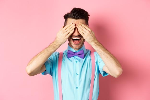 쾌활 한 젊은 남자 축 하, 닫힌 된 눈과 행복 한 미소로 놀람을 기다리고, 분홍색 배경에 즐거운 서. 프리미엄 사진
