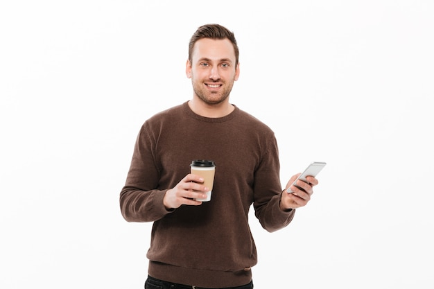Cheerful young man drinking coffee and chatting Free Photo