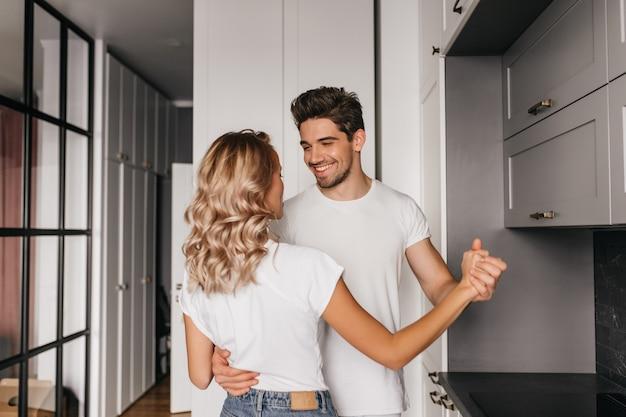 Веселый молодой человек нежно обнимает свою девушку. пара танцует на кухне в выходные утром. Бесплатные Фотографии