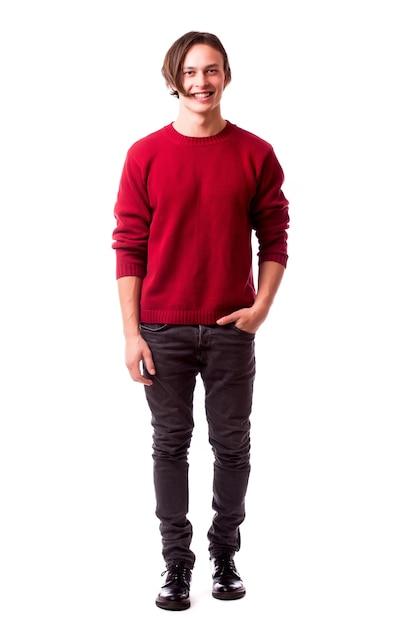 주머니에 손을 잡고 흰 벽에 서있는 동안 정면을보고 쾌활한 젊은 남자 무료 사진