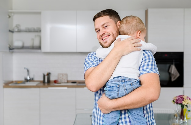 Cheerful young man hugging a child Free Photo