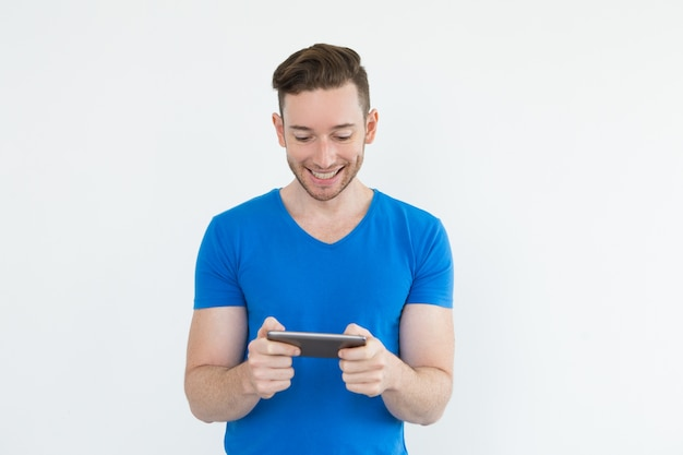 Cheerful young man playing video game on tablet Free Photo