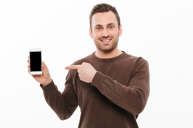 Cheerful young man showing display of mobile phone Free Photo