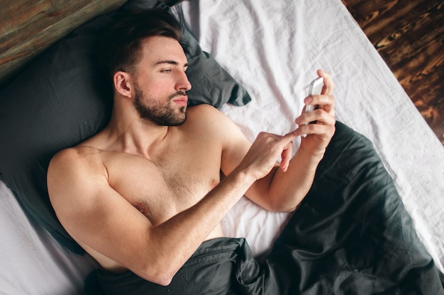 Cheerful young man speaking by cellphone in bedroom. handsome sporty young guy in underwear is lying on bed Premium Photo