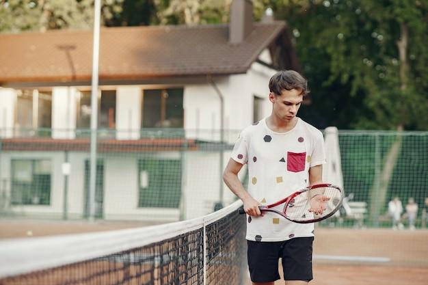 Allegro giovane uomo in maglietta. ragazzo con racchetta da tennis e palla. Foto Gratuite