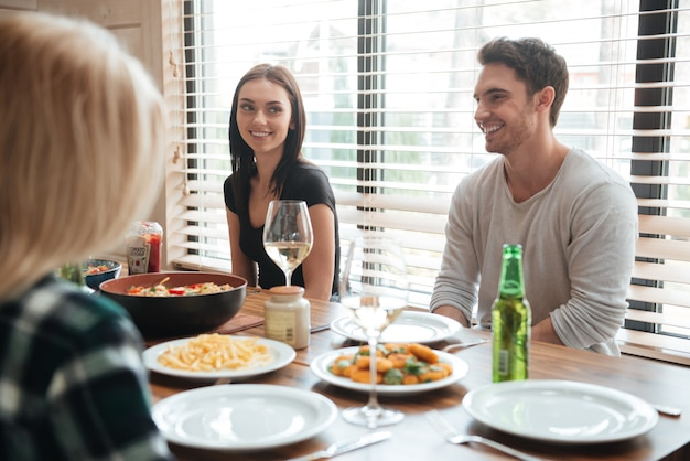 Cheerful young people enjoying meal while sitting at the dinning table Premium Photo