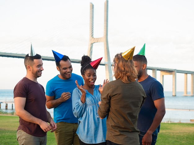 Cheerful young people giving present for surprised girl. smiling friends congratulating young woman with birthday.  concept of birthday party Free Photo