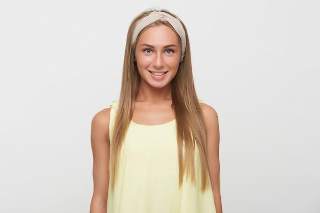 매력적인 미소로 카메라를 행복하게보고 Hatural 메이크업과 쾌활한 젊은 꽤 긴 머리 금발의 여자, 캐주얼에 흰색 배경 위에 서 무료 사진