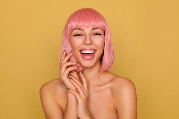 Cheerful young pretty pink haired woman laughing happily while looking  and folding raised hands while posing over mustard wall Free Photo