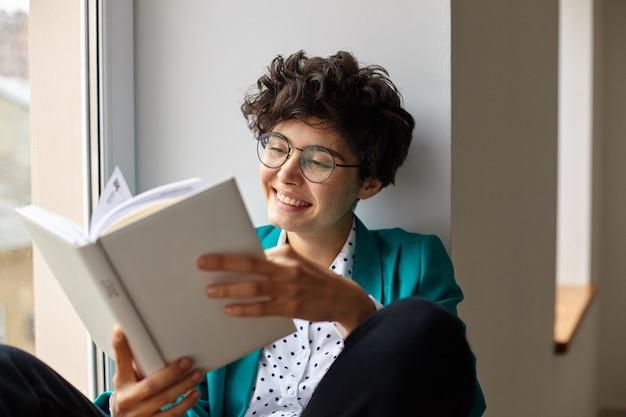 쾌활한 젊은 짧은 머리 곱슬 갈색 머리 여성 트렌디 한 우아한 옷을 입고 큰 창 위에 앉아 좋은 분위기에 있고 행복하게 웃는 동안 책을 읽고 무료 사진