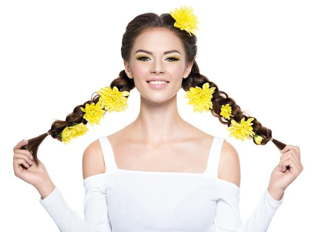 Giovane bella donna sorridente allegra con le trecce lunghe. ritratto di moda. ragazza attraente con trucco giallo brillante - isolato su bianco. trucco professionale. acconciatura d'arte. Foto Gratuite