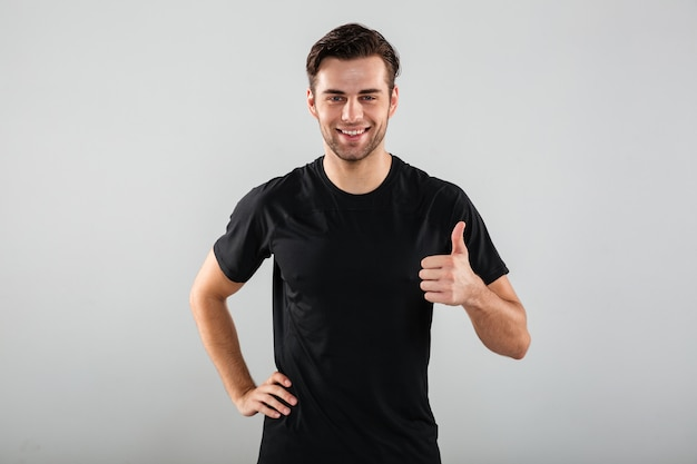 Cheerful young sports man posing showing thumbs up gesture. Free Photo