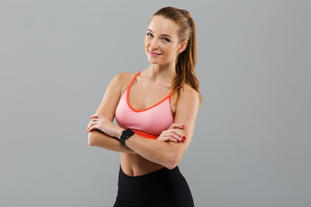 Cheerful young sports woman with arms crossed. Free Photo