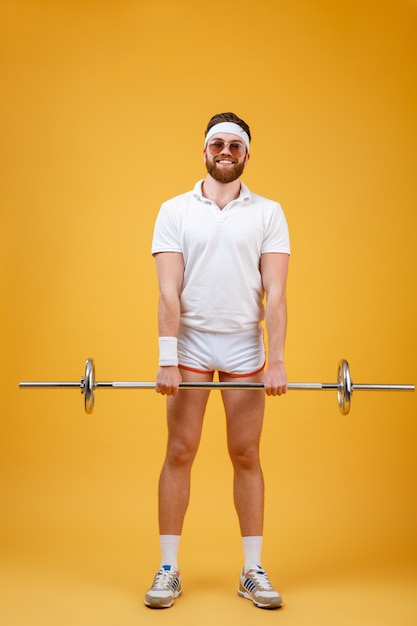 Веселый молодой спортсмен делает спортивные упражнения со штангой Бесплатные Фотографии