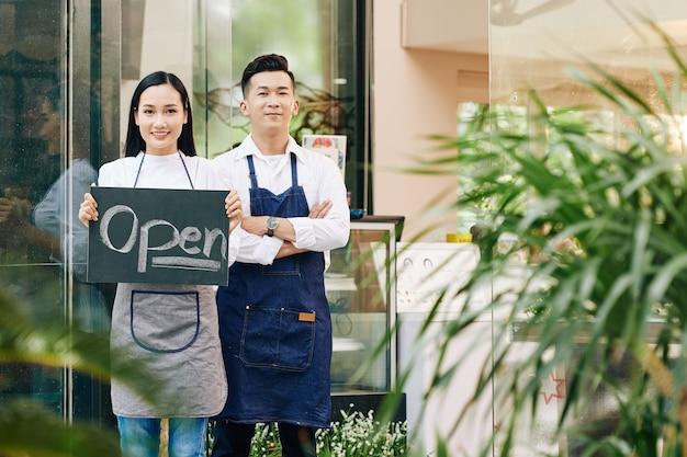 검역 및 고객 초대 후 카페를 여는 쾌활한 젊은 베트남 웨이터 프리미엄 사진