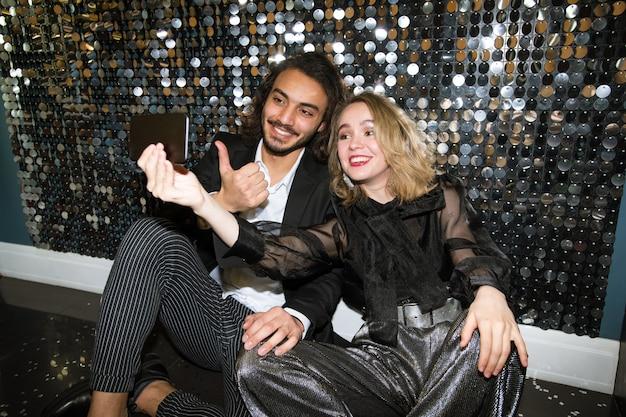 Веселая молодая хорошо одетая пара делает селфи, сидя у сверкающей стены в ночном клубе на вечеринке Premium Фотографии