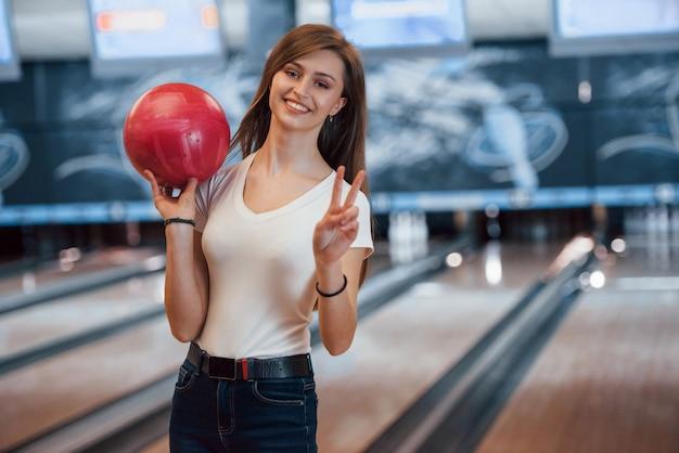 Giovane donna allegra in abbigliamento casual che tiene palla da bowling rossa nel club Foto Gratuite