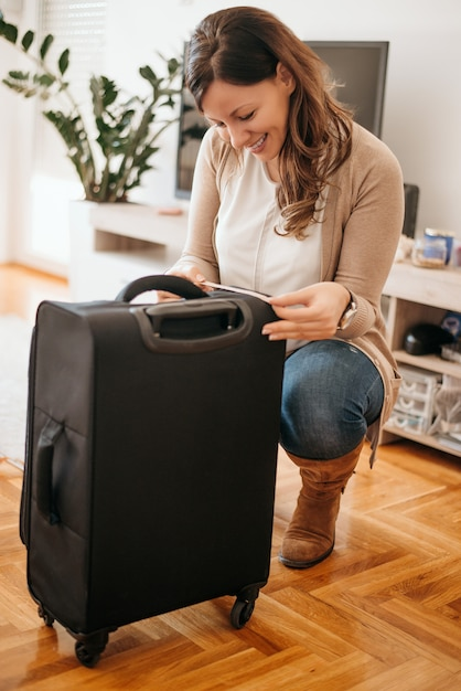 Cheerful young woman doing inspection of luggage. measuring luggage before going on holiday. Premium Photo