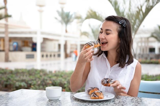 Giovane donna allegra che gode del caffè del mattino con ciambelle sulla terrazza all'aperto. Foto Gratuite