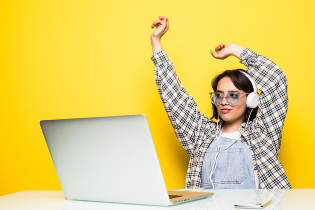 Cheerful young woman in headphones dancing to music while sitting in front of computer Free Photo