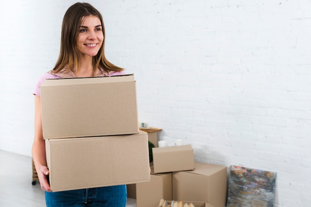 Cheerful young woman holding cardboard boxes in her new house Free Photo