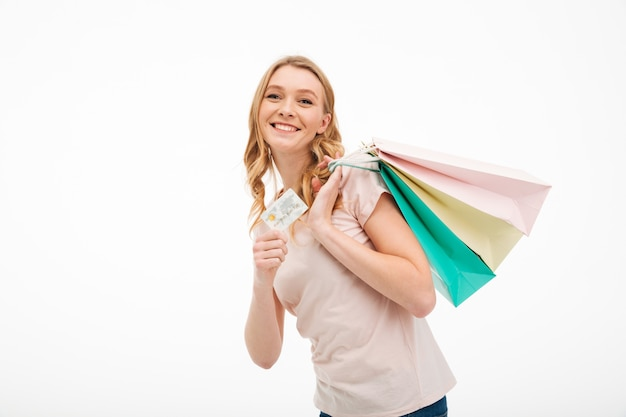 Cheerful young woman holding credit card and shopping bags. Free Photo