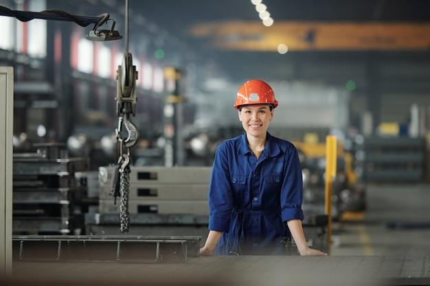 현대 산업 공장에서 작업하는 동안 작업복과 보호용 헬멧에 쾌활한 젊은 여자가 당신을 찾고 프리미엄 사진