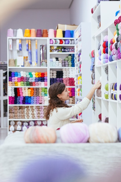 Cheerful young woman organizing shelves at a retail business Premium Photo