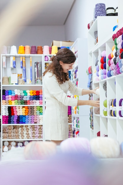 Cheerful young woman organizing wools at a retail business Premium Photo