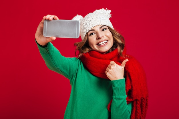 Cheerful young woman showing thumbs up. Free Photo