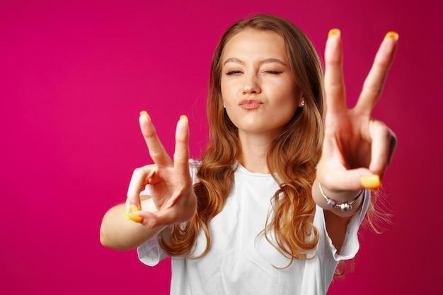 勝利の手サインを示す陽気な若い女性 Premium写真