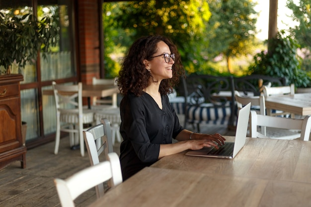 Веселая молодая женщина, сидящая за столом, печатающая на ноутбуке Premium Фотографии
