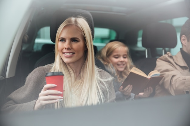 Cheerful young woman sitting in car Free Photo