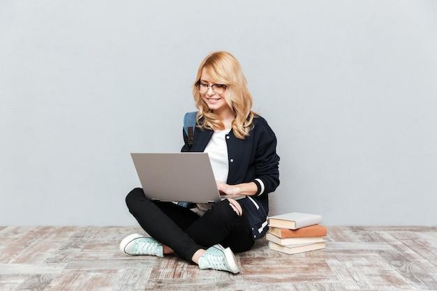 Жизнерадостный студент молодой женщины используя портативный компьютер. Бесплатные Фотографии
