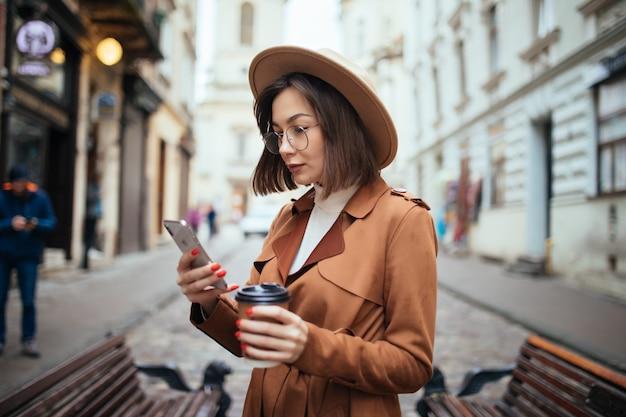 Пальто жизнерадостной молодой женщины нося гуляя outdoors держащ кофейную чашку на вынос Бесплатные Фотографии
