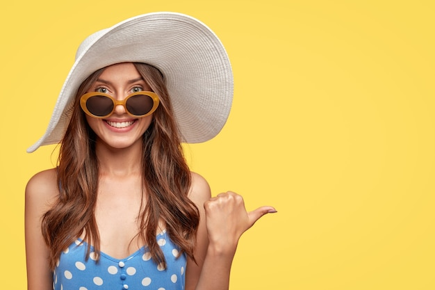 Cheerful young woman wearing a hat posing against the yellow wall Free Photo