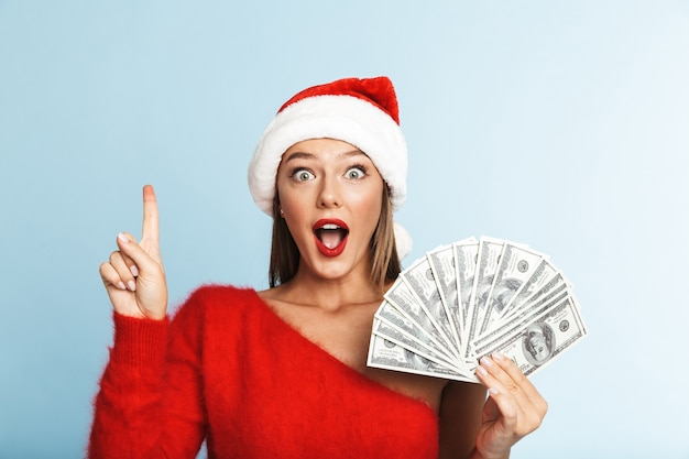 Cheerful young woman wearing santa claus hat, showing money banknotes, pointing finger up Premium Photo