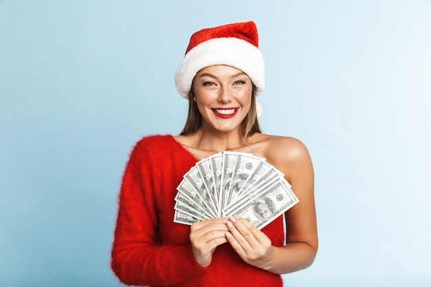 Cheerful young woman wearing santa claus hat, showing money banknotes Premium Photo