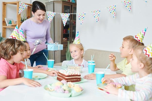 小さな子供たちのグループとのテーブルのそばに立って、ホームパーティーでの関係を作る誕生日プレゼントを持つ陽気な若い女性 Premium写真