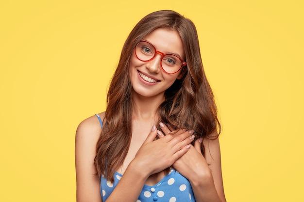 Giovane donna allegra con gli occhiali in posa contro il muro giallo Foto Gratuite