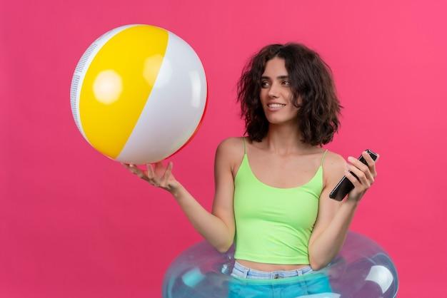 Una giovane donna allegra con i capelli corti nella parte superiore del raccolto verde che esamina il telefono mobile della tenuta della palla gonfiabile Foto Gratuite