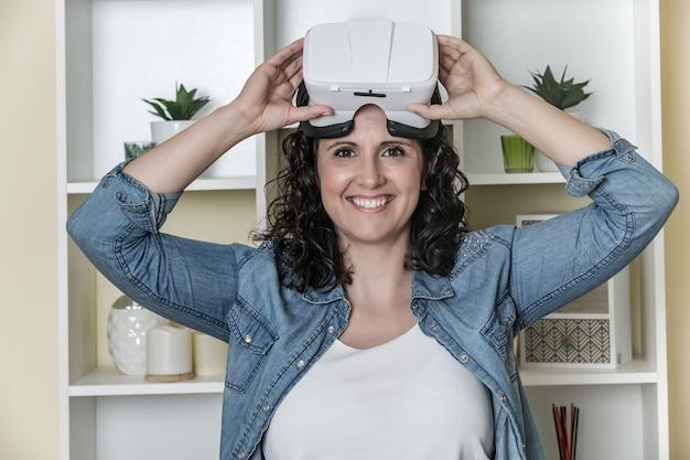 光の現代的なオフィスで仮想現実の眼鏡を持つ陽気な若い女性 Premium写真